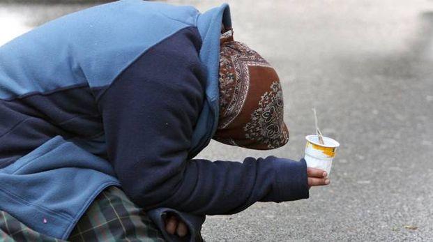 Una mendicante chiede l'elemosina (Foto archivio)