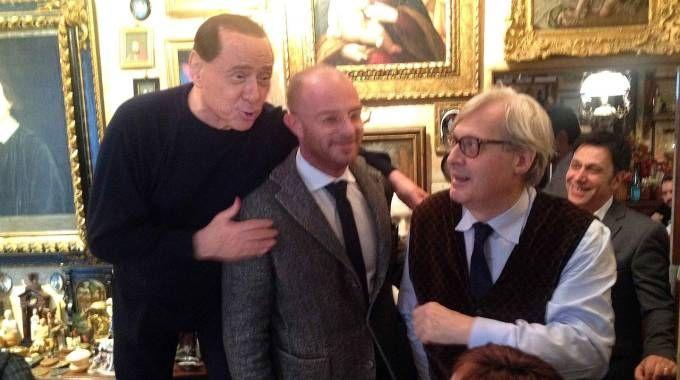 Silvio Berlusconi sale su una sedia per essere più alto del sindaco di Ro Antonio Giannini. A destra Vittorio Sgarbi