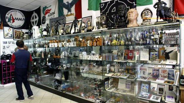 SOUVENIR IN VETRINA Alcuni dei numerosi oggetti e bandiere in vendita nella città di Mussolini (Frasca)