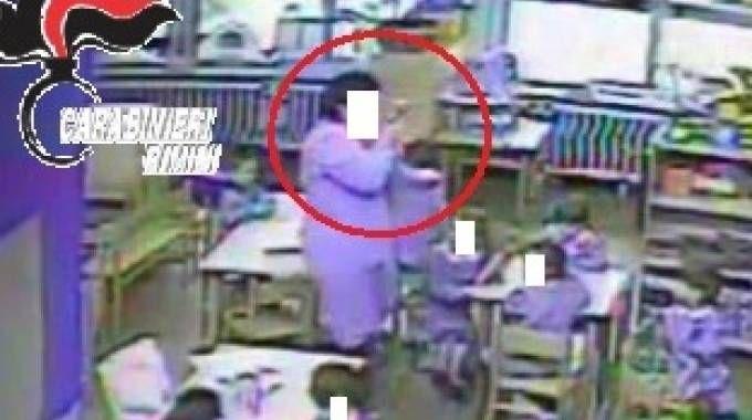 Uno sconvolgente fermo immagine dei maltrattamenti avvenuti all'asilo 'Il delfino': la maestra Loredana Pacassoni  è ora ai domiciliari