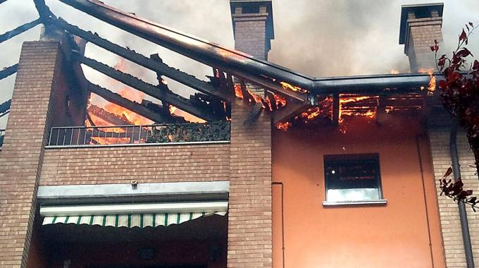 Le fiamme all'altezza del tetto; a sinistra, uno dei pompieri impegnati nell'intervento