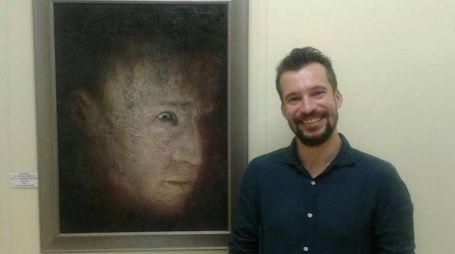 Carlo Alberto Vandelli di fianco a un suo ritratto