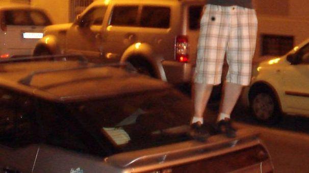 Un giovane sopra un'auto in una foto d'archivio Newpress