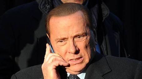 Silvio Berlusconi parla al telefono mentre sale in auto dalla sua abitazione nel centro di Milano in una foto d'archivio. ANSA/ DANIEL DAL ZENNARO