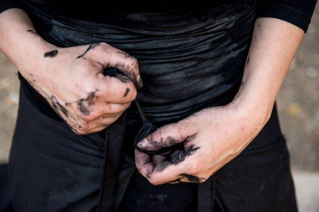 Così l'artista spiega mani e volto sporchi di nero