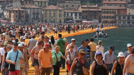 People walk the 'The Floating Piers' by Bulgarian artists Christo and Jeanne-Claude on Lake Iseo during the last day of the art work near Sulzano, northern Italy, 03 July 2016. The 'Floating Piers' with their bright orange covers will be open until 03 July and will connect the two towns Sulzano and Monte Isola. ANSA/Simone Venezia