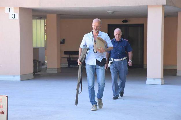 La polizia con il fucile sequestrato all'uscita dall'appartamento. Non è l'arma del delitto