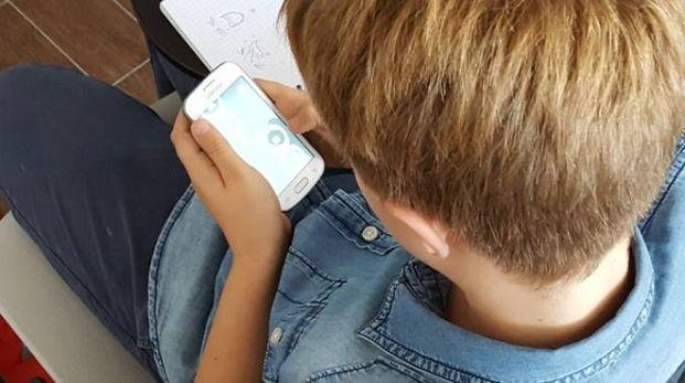 Un ragazzino con un cellulare