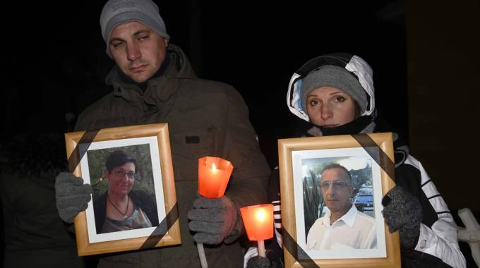 Coniugi uccisi, due partecipanti alla fiaccolata con in mano le foto delle vittime (Bp)