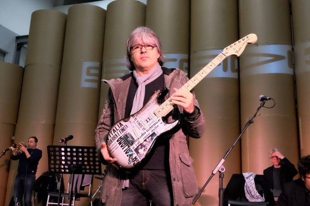 Andrea Fornili e la chitarra con stampate pagine del Resto del Carlino  (fotoSchicchi)