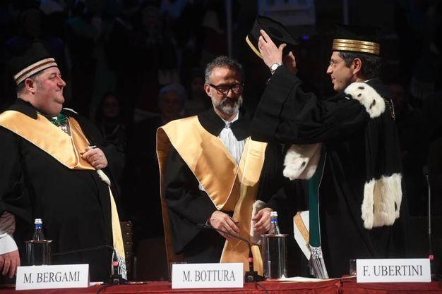 Francesco Ubertini posa il tocco sul capo di Bottura (schicchi)