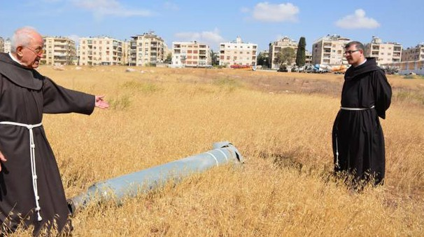 Padre Firas Lutfi (a destra) davanti a un razzo. Sullo sfondo la città di Aleppo