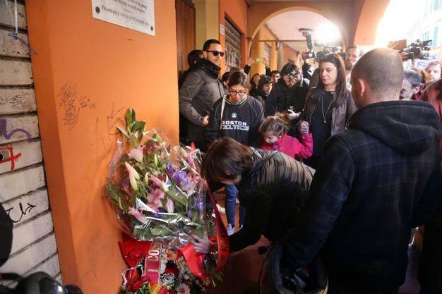 Tanti fiori deposti alla lapide in via Mascarella (foto Schicchi)