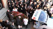 Il feretro lascia la chiesa tra gli applausi (foto Isolapress)