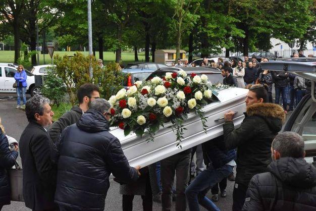Il feretro, coperto di rose bianche e rosse, viene portato in chiesa (foto Artioli)