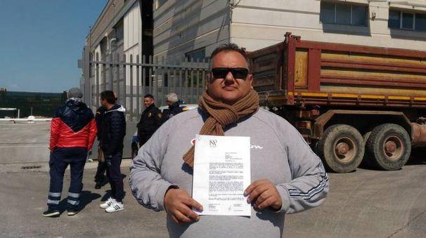 Emiliano Fava mostra la lettera di licenziamento ricevuta. E' stato fotografato davanti alla sua azienda