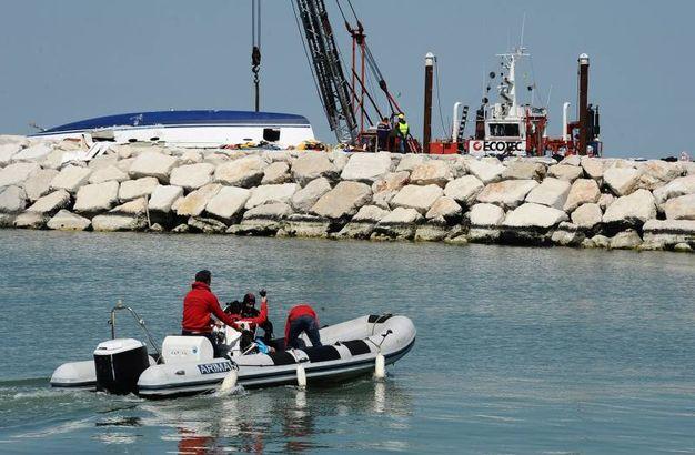 Nel molo uno speciale pontone rimuove il relitto della barca (foto Manuel Migliorini)