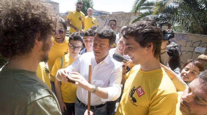 Matteo Renzi con i volontari delle magliette gialle (Ansa)