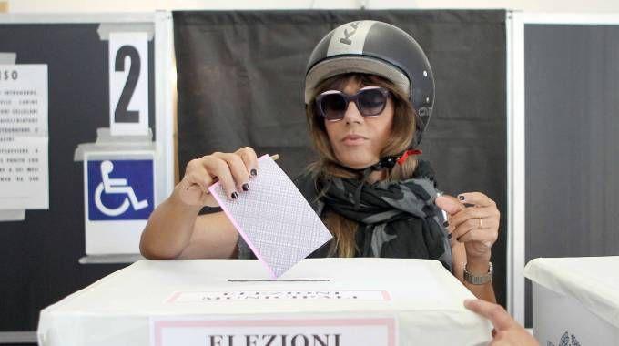Parvin Tadjk, la moglie di Grillo al voto, anche lei con il casco (LaPresse)