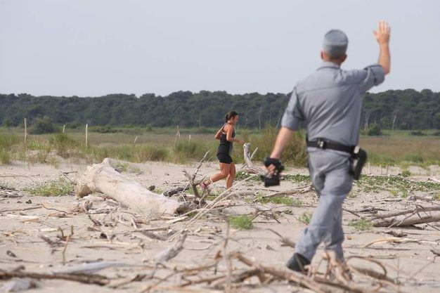 Un carabiniere richiama una giovane podista straniera che correva nell'area protetta, ignara dei divieti (foto Zani)