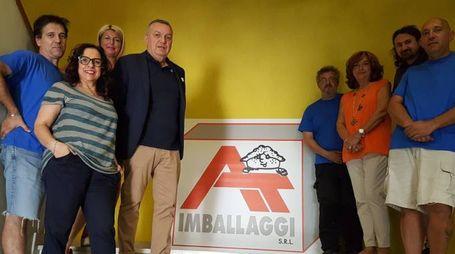 Lino Boschi, a sinistra del logo, con i dipendenti dell'azienda alle Roveri