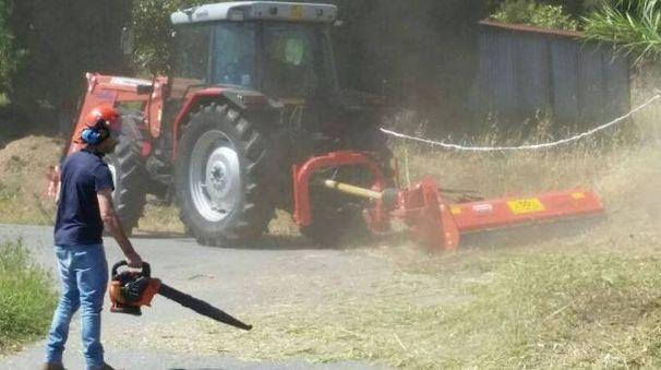 L'assessore Federico Sebastiani ripulisce una strada dopo il passaggio dell'unico mezzo disponibile per tagliare l'erba