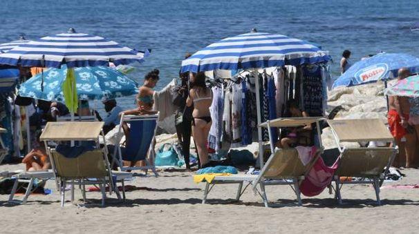 Il mercato abusivo in spiaggia, fotografato sabato: ogni giorno è così