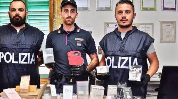 Gli agenti del commissariato mostrano i profumi contraffatti sequestrati