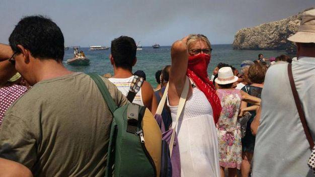 I turisti  salgono a bordo di imbarcazioni per lasciare il viallaggio (Ansa)
