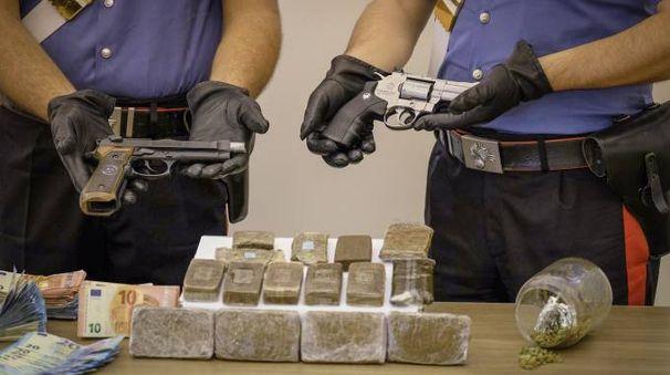 I militari mostrano droga e pistole confiscate