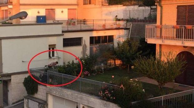 Il ladro mentre scavalca la recinzione del giardino