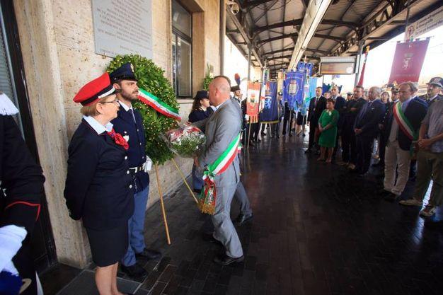 Una corona di fiori posta in stazione in ricordo della strage (Foto Schicchi)
