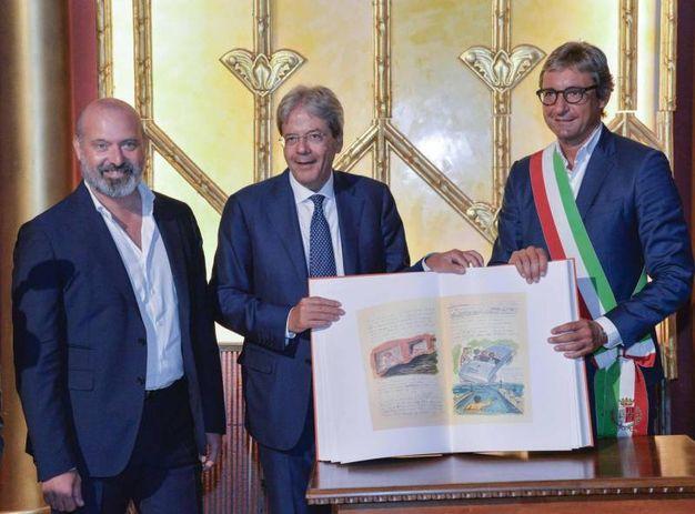 Gentiloni sfoglia il 'Libro dei sogni' di Federico Fellini durante la visita al ristrutturato Cinema Fulgor di Rimini (foto Ansa)