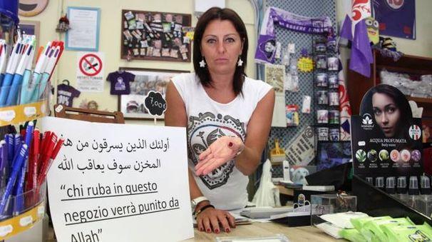La commerciante col cartello contro i ladri (foto NewPressPhoto)