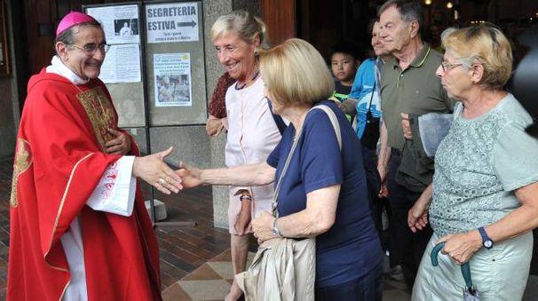 Monsignor Mario Delpini  saluta e parla  con i fedeli all'uscita della chiesa