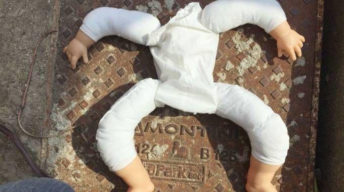 La bambola senza testa trovata sull'auto dei servizi sociali del comune di Vallefoglia (Fotoprint)