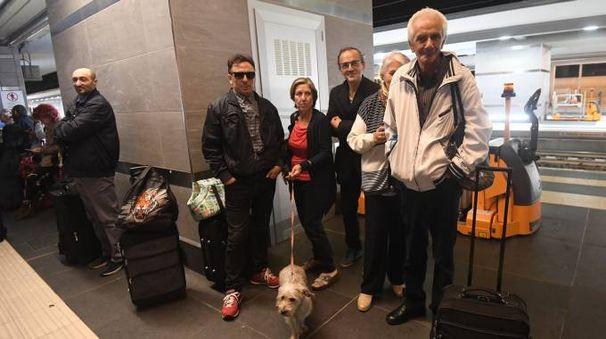 Alcuni viaggiatori in stazione