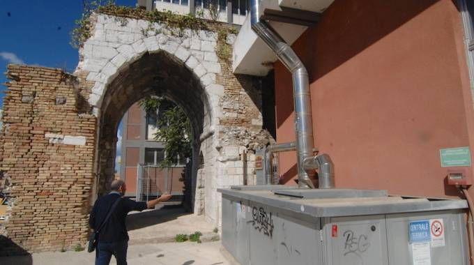 Muri sgretolati e degrado dietro l'arco