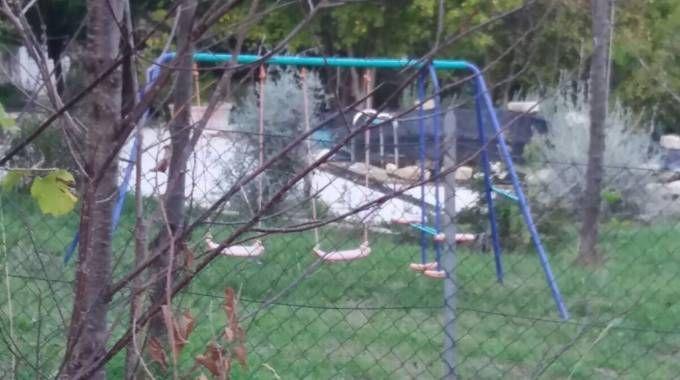 Dietro le altalene la piscina coperta dal telo nero dove è caduto il bambino