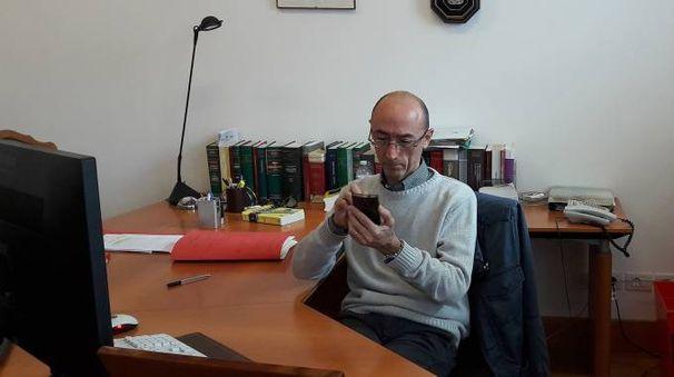 Il giudice del Lavoro Maurizio Paganelli mentre consulta l'agenda elettronica sul telefono