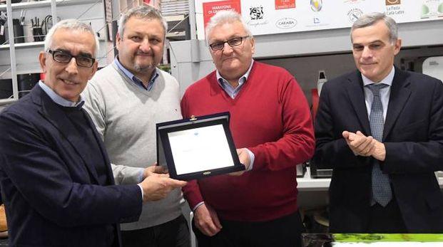 Il presidente di Ascom Enrico Postacchini consegna a Mauro e Gianni Guizzardi una targa-riconoscimento per gli oltre 70 anni di attività