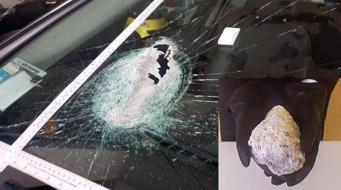 Il sasso e il parabrezza dell'auto sfondato