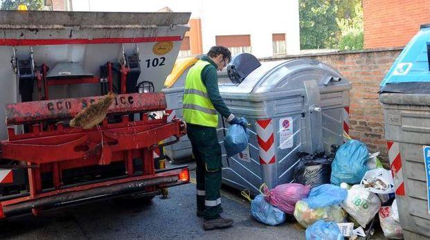 Un addetto raccoglie il pattume abbandonato per strada (foto Businesspress)