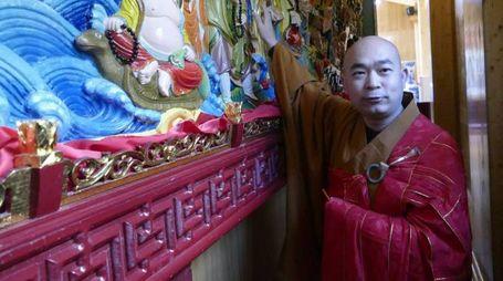 Un monaco buddista del tempio di piazza della Gualchiera mostra la nuova opera  di legno dipinto in rilievo collocata  dietro l'altare