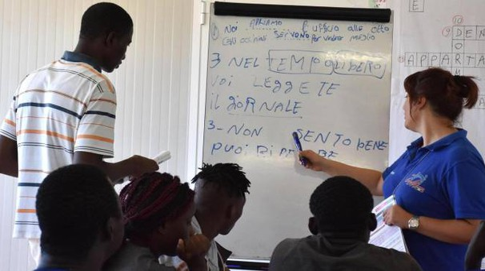 Alcuni migranti a lezione di lingua italiana (archivio Ansa)