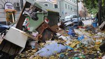 Rifiuti sparsi presso un cassonetto in una strada di Genova (Ansa)