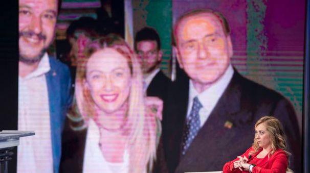 Giorgia Meloni e sullo sfondo Berlusconi e Salvini (ImagoE)