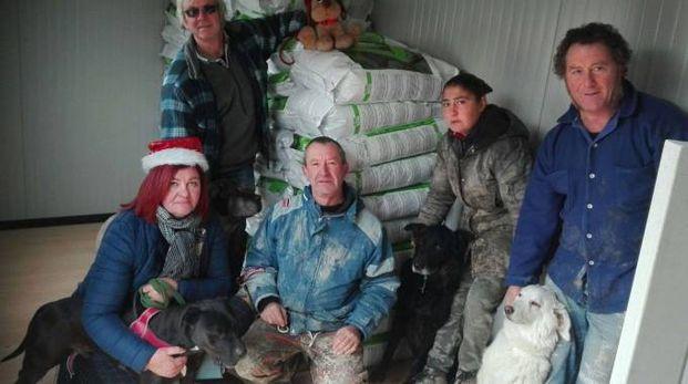 I volontari del canile di Ossaia con alle spalle le crocchette donate da Jovanotti
