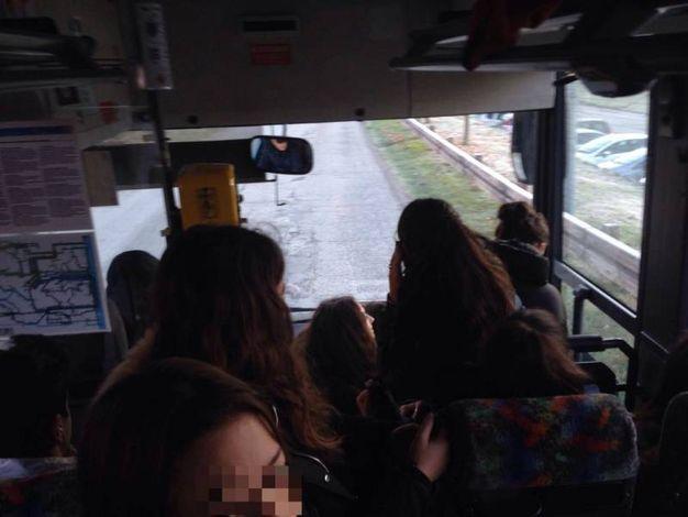 Alcuni ragazzi si sono seduti sui gradini di ingresso dell'autobus