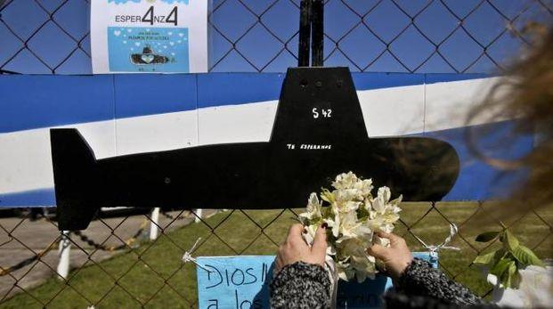 Una donna lascia i fiori alla base navale di Mar de Plata (Ansa)